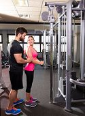 stock photo of pulley  - cable pulley system personal trainer man and woman learning at fitness gym - JPG
