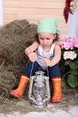 foto of kerosene lamp  - Beautiful small girl holding kerosene lamp on country style background - JPG