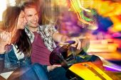 stock photo of car ride  - Young couple in love in a bumper car  - JPG