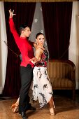 Young dance couple preforming latin show dance in beautiful ancient ballroom poster