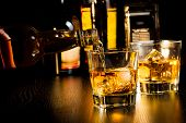 picture of whiskey  - barman pouring whiskey in front of bottles on wood table focus on top of bottle - JPG