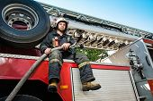 image of firefighter  - Firefighter sitting on a firefighting truck with water hose  - JPG