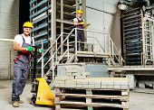 foto of heavy equipment operator  - Young worker moving paving stones with pallet truck on a factory - JPG