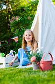 stock photo of tipi  - Adorable little girl having fun playing outdoors on summer day - JPG