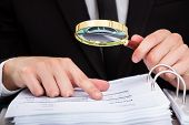 foto of investigation  - Businessman Looking At Document Through Magnifying Glass - JPG
