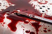 picture of autopsy  - Surgeon knife on stainelss steel autopsy table with lot of blood - JPG