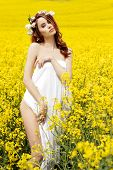 stock photo of carnal  - Young attractive sexy girl on a sunny day of flowering rape field with flowers in red hair - JPG