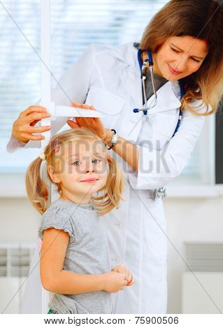 Doctor Measuring Height Of A Cute Redhead Girl.
