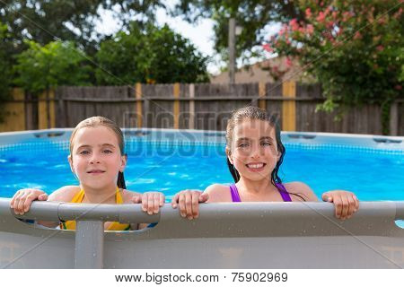 kid girls swimming in the pool in backyard happy