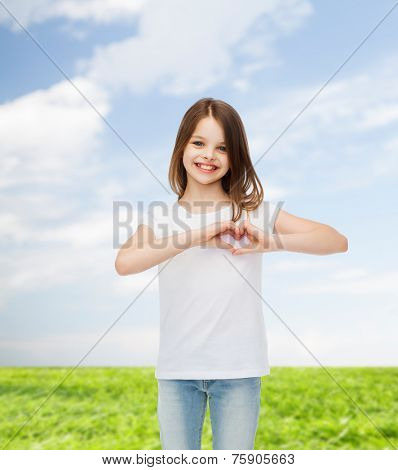 advertising, childhood, summer, gesture and people concept - smiling little girl in white blank t-shirt making heart-shape gesture over natural background