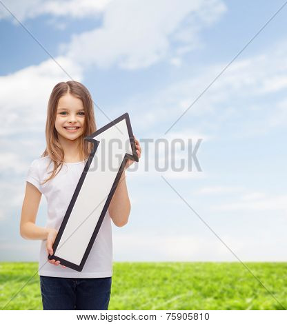 advertising, direction, summer vacation and childhood concept - smiling little girl with white arrow pointing up over natural background