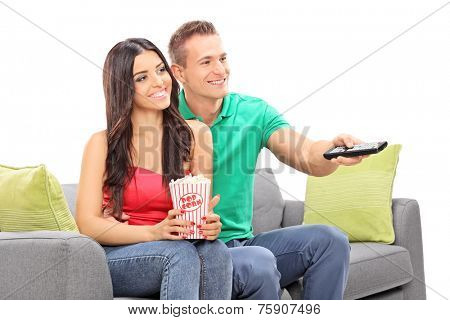 Young couple watching TV seated on a sofa isolated on white background