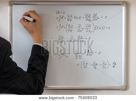 Teacher Writing Math Equations On Whiteboard