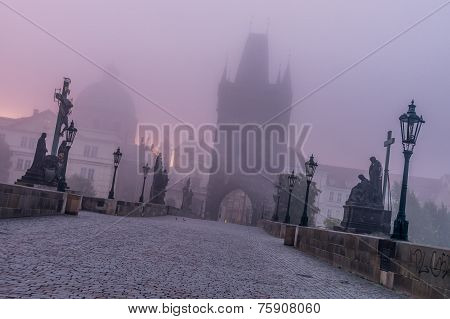 Charles Bridge In Foggy Morning In Prague
