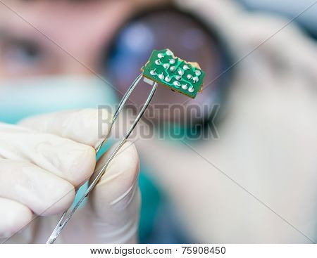 Scientist Examinates Electronic Circuit