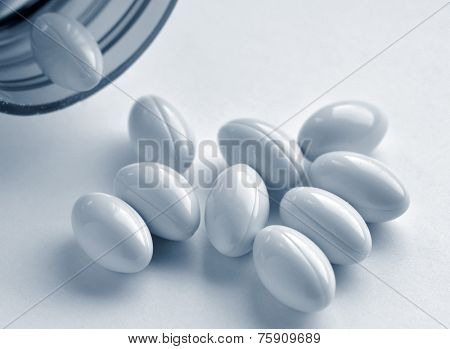 Closeup of vitamin pills and bottle. Image toned blue for effect.