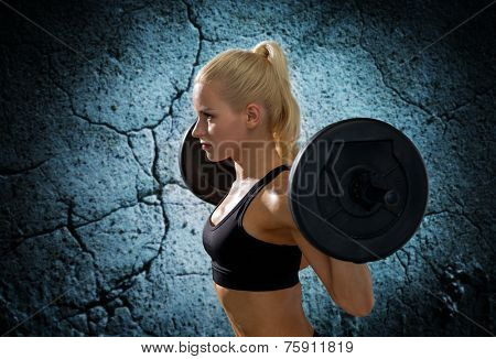 fitness, sport, powerlifting and people concept - sporty woman exercising with barbell over concrete wall background