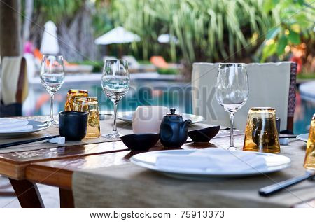 Close Up of Table Place Settings at Outdoor Poolside Asian Restaurant
