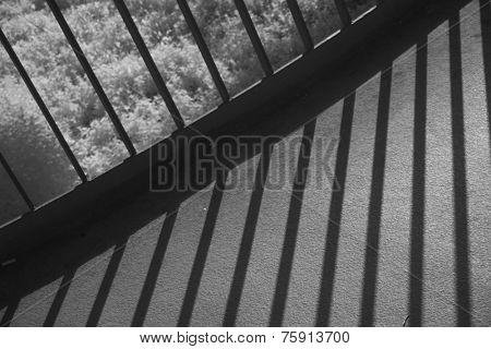 Metal railing throwing shadows on footbridge. Black and white infrared shot taken with OLYMPUS digital camera.