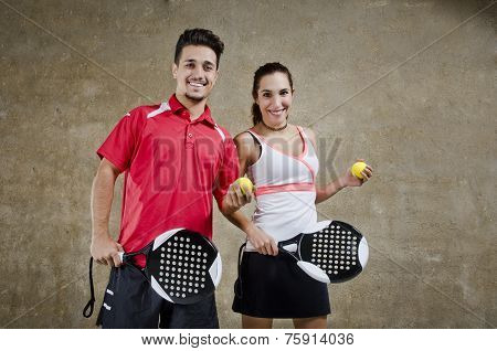 Paddle Tennis Couple Posing In Concrete Court