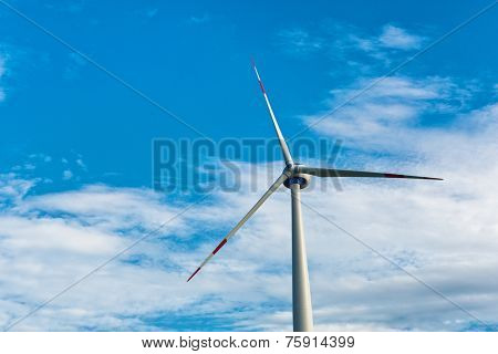 Single wind turbine providing sustainable energy and electricity by converting the kinetic energy of the wind using a natural resource against a blue sky with copyspace