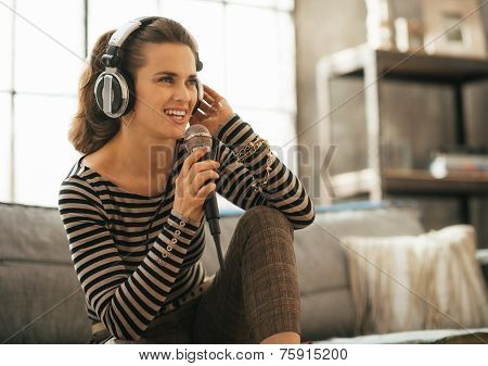 Portrait Of Happy Young Woman Singing With Microphone In Loft Ap