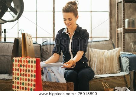 Happy Young Woman With Shopping Bags In Loft Apartment Checking