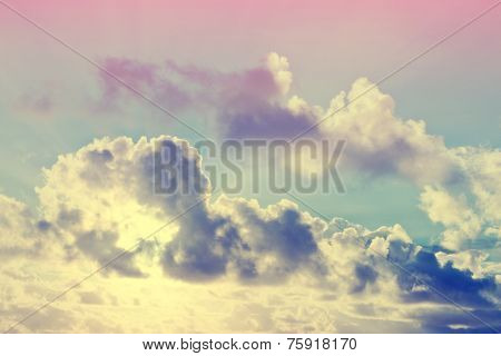 Ethereal cloudscape with glowing clouds and a colorful pink flare in a blue sky for a beautiful atmospheric spiritual background