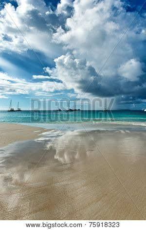 Spectacular cloud formations over Anse Lazio Beach in the Seychelles reflected in the thin film of water on the golden sand below