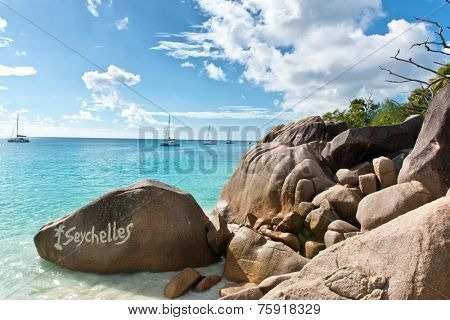 Close up Old Granite Rocks at Captivating Anse Lazio Beach in Seychelles. Captured with Boats Afar on Blue and White Clouds Above.