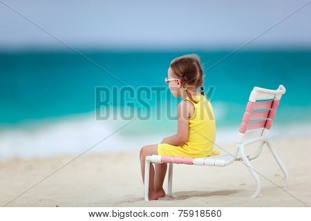 Adorable little girl sitting on chair at tropical beach