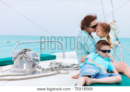 Family of mother and her kids having great time sailing at luxury yacht or catamaran boat