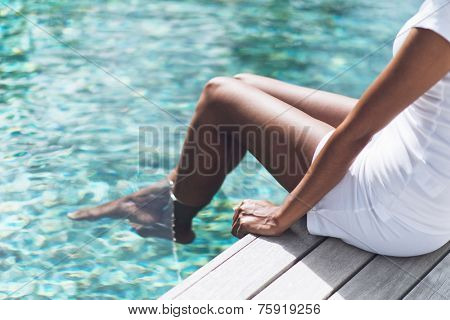 Close up Asian Indian Woman in White Casual Outfit Resting at Poolside with Both Feet on Clear Water