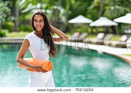 Attractive Asian woman on a tropical summer vacation standing at a resort hotel in front of a sparkling blue pool with a rolled towel under her am looking back with a happy smile