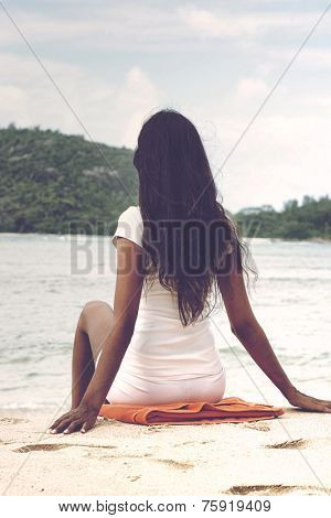 Close up Rear View Shot of Long Hair Woman in White Casual Outfit Sitting on White Beach Sand with Orange Towel. Captured with Hands on the Side while Facing the Enchanting Beach.