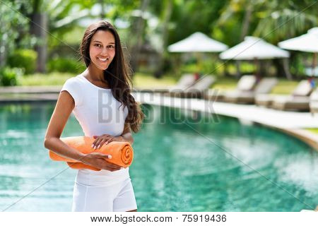 Pretty young Indian woman at a tropical resort standing in front of a sparkling pool with beach umbrellas with a rolled orange towel under her arm smiling at the camera