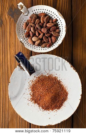 cocoa powder and roasted cocoa chocolate beans in old enamel sieve, textured  wooden background