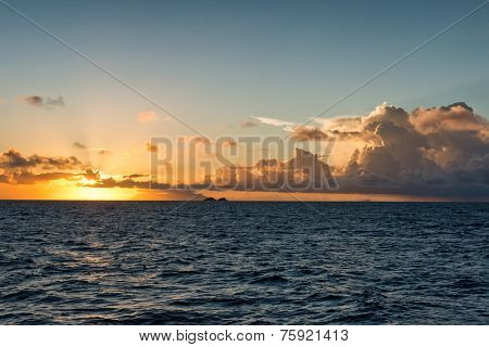 Colorful marine sunset over a tropical ocean with the fiery orange sun dipping down towards the horizon with low lying cumulus cloud formations in a twilight sky