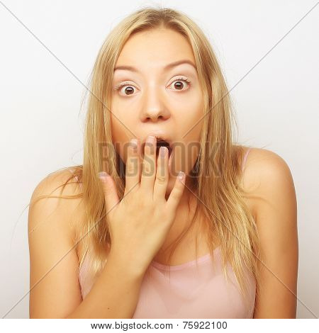 Close-up portrait of surprised blond girl holding her head in amazement and open-mouthed.
