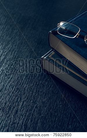 pile of books and glasses symbolizing the concept reading habit or studying