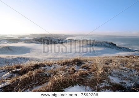 Icy Snow Covered Links Golf Course And Sea