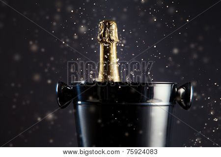 Concept of celebration. Unopened bottle of champagne in metal container