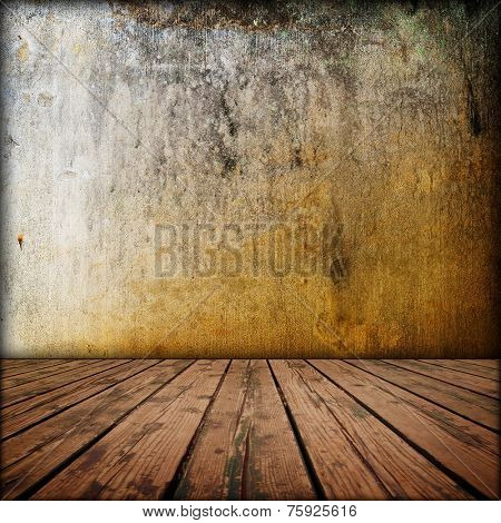 Grungy old yellowish wall with wooden worn floor.