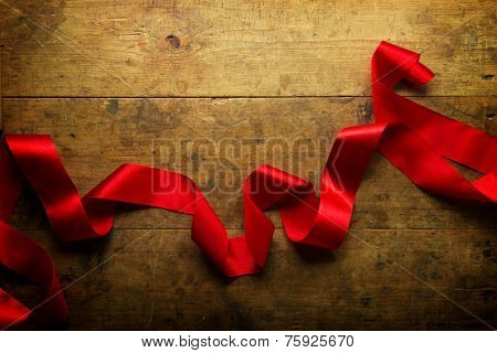 Freely uncurled red ribbon on a rustic wood background