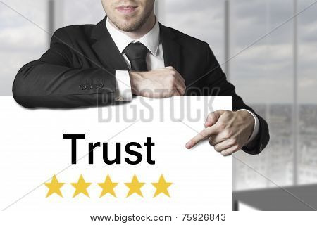 Businessman Pointing On Sign Trust