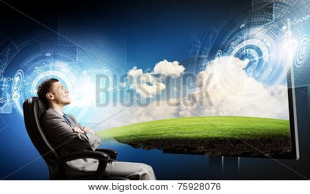 Young businessman sitting in chair behind media screen