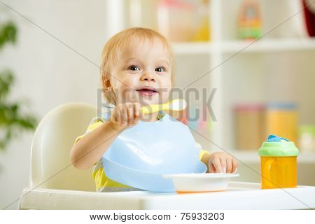 funny baby boy eating by itself with spoon