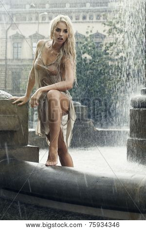 Sexy Young Wet Woman In City Fountain In Rain