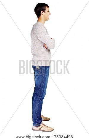Full length right side view portrait of smiling young man in glasses and beige sweater with crossed arms on his chest isolated on white background