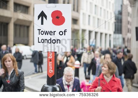 LONDON, UK - NOVEMBER 08: Street sign with red poppy pointing to the Tower of London. November 08, 2014 in London. The ceramic poppies installation was created to mark the centenary of WWI's outbreak.